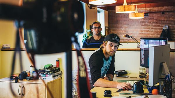 Male Visual Communication Design student with baseball cap at internship at Driven Studios in Burlington, Vermont