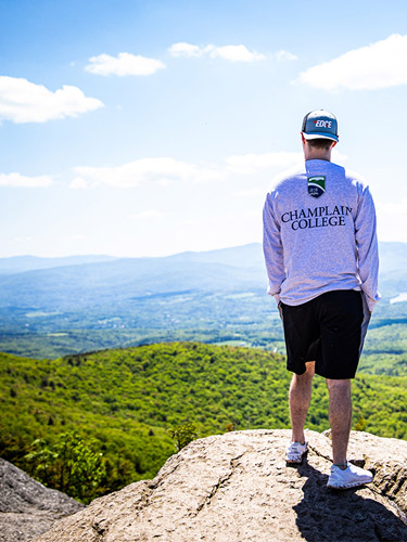Champlain student standing on top of Stowe Pinnacle