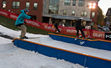 Champlain College student snowboarding on campus