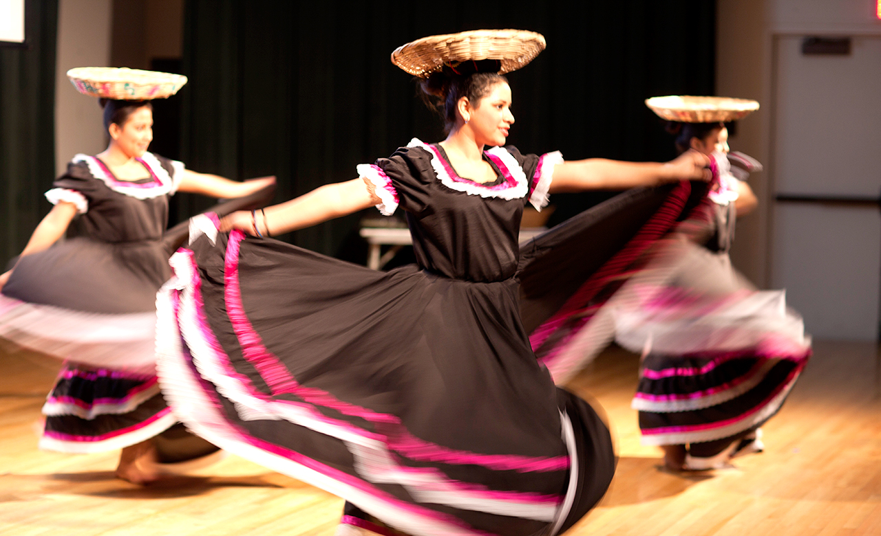 3 women dancing as part of a cultural presentation
