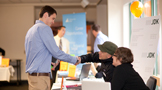 a Champlain College student shaking hands with an employer at the internship fair