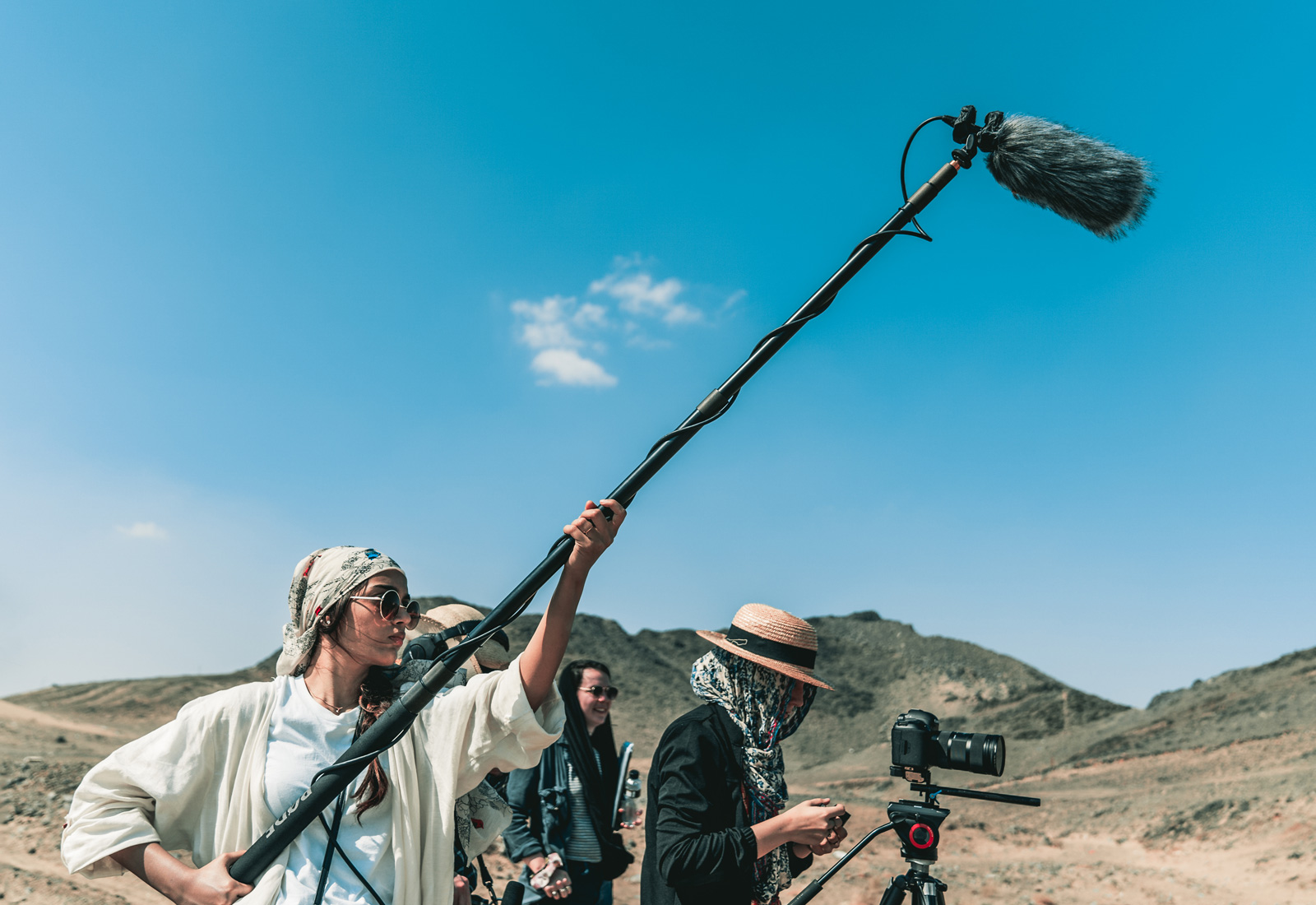 Champlain College filmmaking students on location in Saudi Arabia. Student in desert with a boom mike lifted high in the air against a very blue sky.