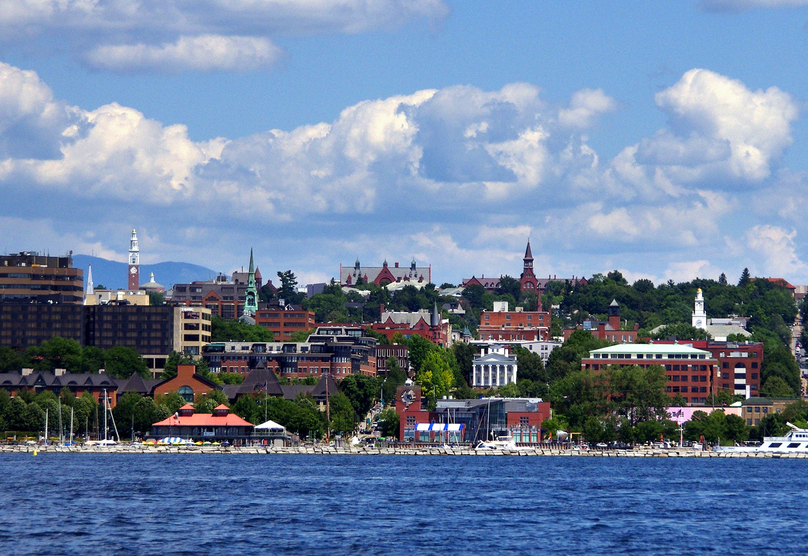 Burlington, Vermont: A view of the downtown area from Lake Champlain with blue sky and fluffy clouds. Champlain College is located in this ideal College Town.
