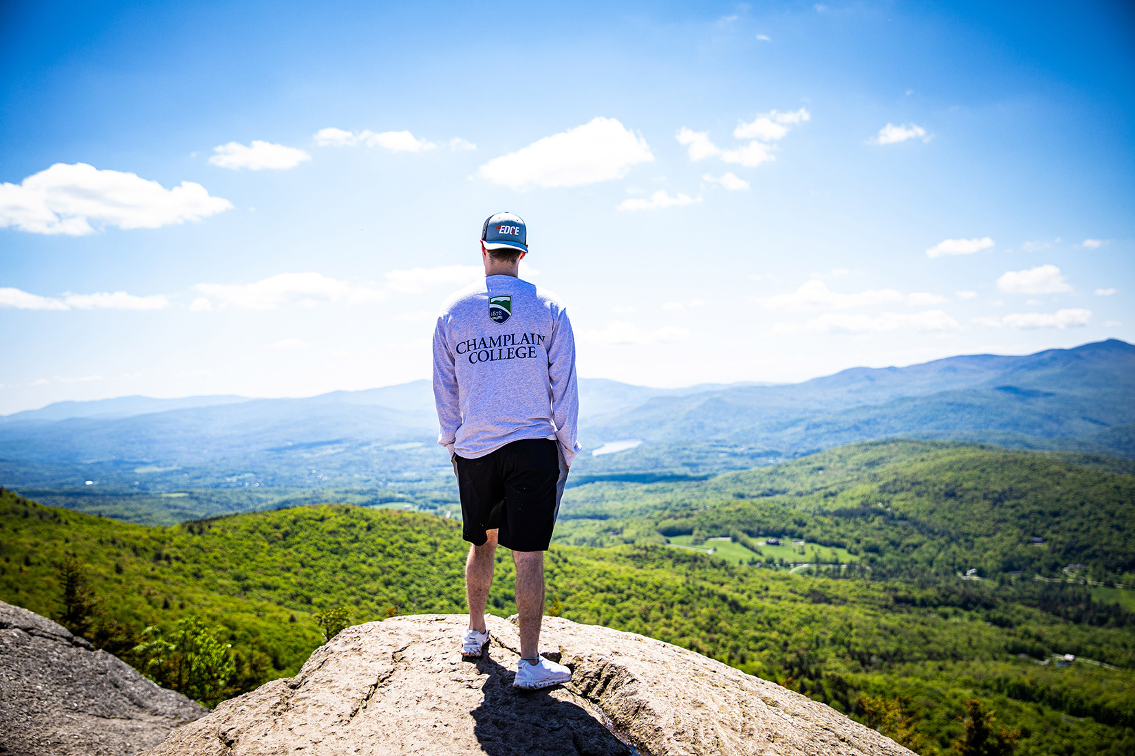 Champlain College student in Champlain College shirt overlooking Pinnacle Ridge in Stowe, Vermont
