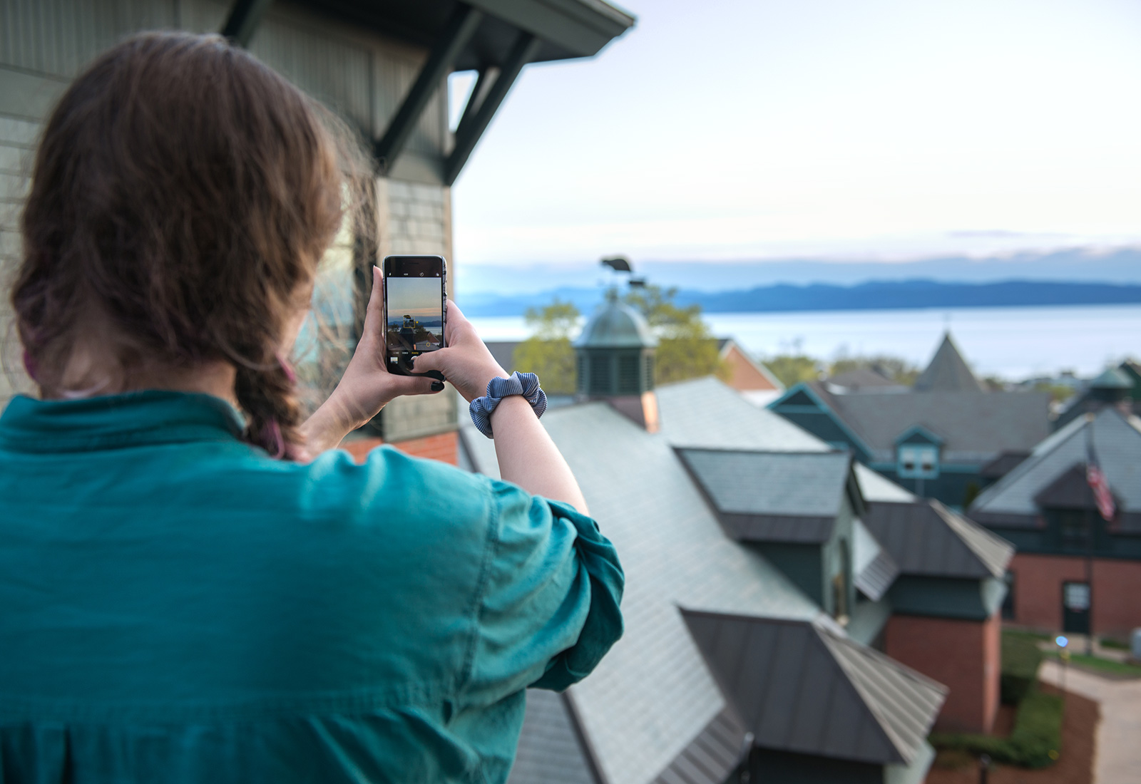 Student taking a shot of the amazing view of Lake Champlain on a spring day from the Miller Information Commons at Champlain College in Burlington, Vermont.
