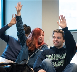 Students at Champlain College raising their hands. Girl with red hair and young man with brown hair and a Champlain College hoodie