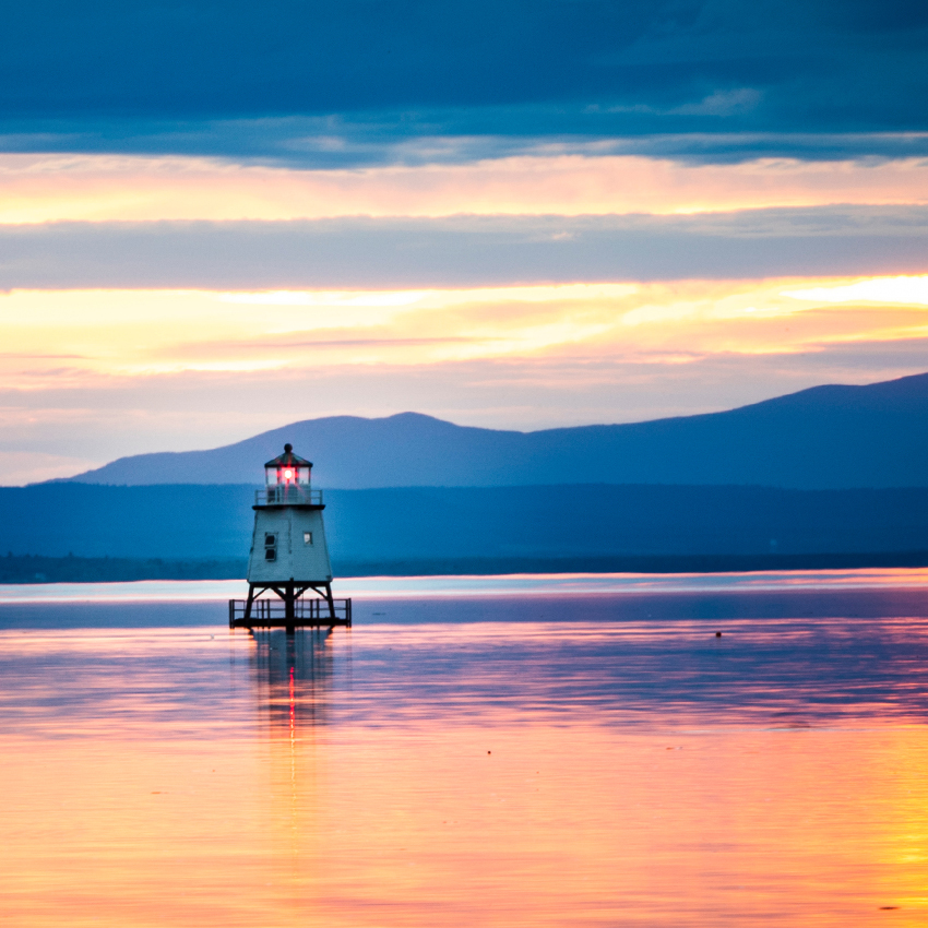 Sunset view of a lighthouse on Lake Champlain and mountains in the distance