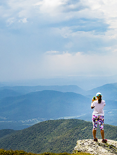 Lone person at the top of Camel's Hump in Vermont, with sun shining down, a wide vista of the mountain range and sky