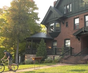 Student on bike outside Champlain College Victorian-era mansion residence hall.