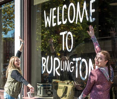 "Two students posing in front of a store window that says ""Welcome to Burlington"""