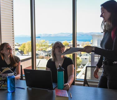 Four students around a table in a common room with a view of Lake Champlain and mountains behind them