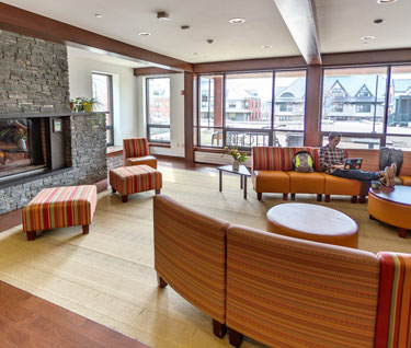 Common room, which features a fireplace and comfy furniture, in an upper-year res hall