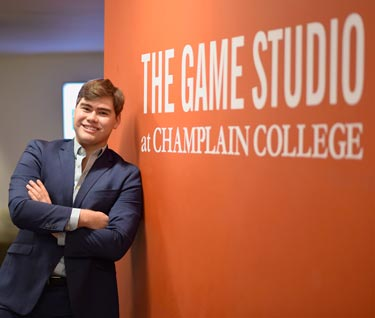 "Student poses in front of a wall on which is written ""The Game Studio at Champlain College"""