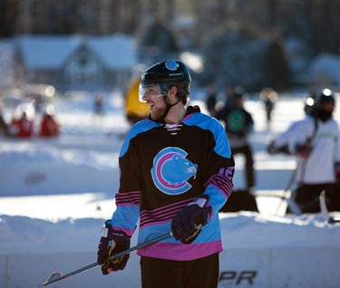 Student hockey player dressed in hockey gear posing with a hockey stick outside on a frozen Lake Champlain