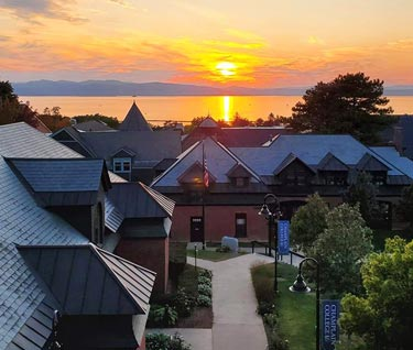 View across campus to sun setting over Lake Champlain