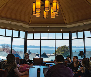 Students collaborate in a study group in the top floor of the library with a view of campus and Lake Champlain in the background.