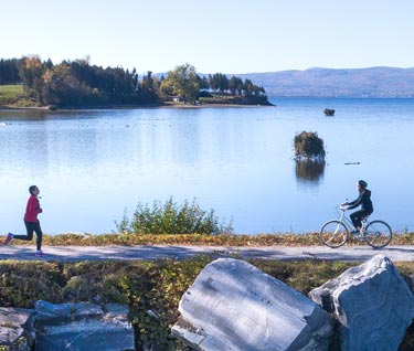View of people jogging and biking on a causeway with Lake Champlain and mountains in the background