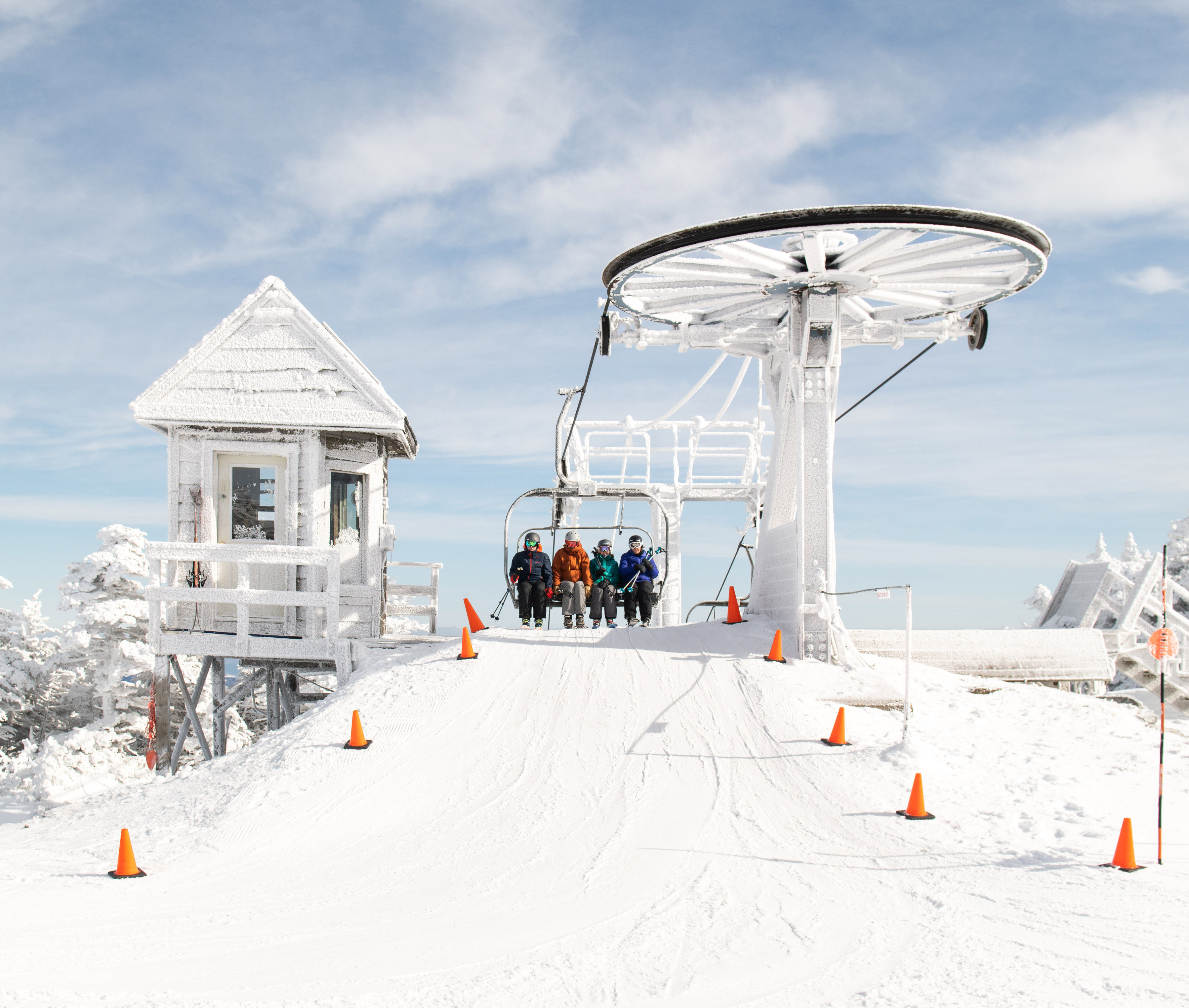 Students riding a ski lift covered in a fresh coat of snow