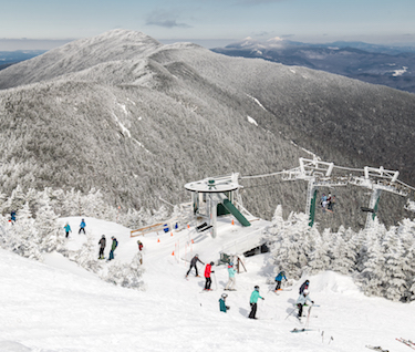 A wide shot of a snowy ski lift; skiiers are readying to go down the mountain