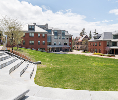 A large, grassy quad with a granite staircase and brick residence halls in view