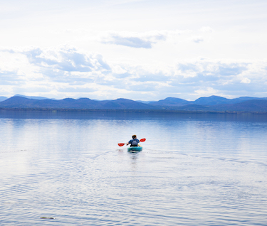 A student kayaks on Lake Champlain with mountains in the distance