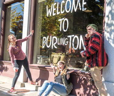 "Three students pose in front of Burton's flagship store with ""Welcome to Burlington"" written on the window."