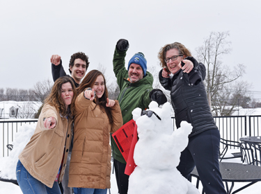 Staff and students with beaver snow sculpture