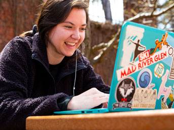 Student working on laptop outside on campus