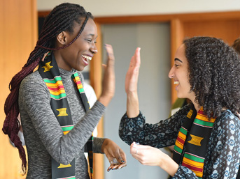 Two students wearing kente cloth sashes giving each other a high-five.