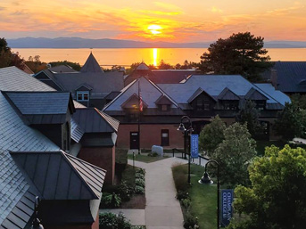 View of campus and buildings with the sun setting over Lake Champlain in the distance.