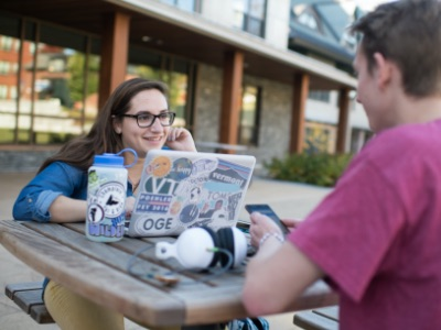 Two Champlain College students sitting with a laptop outside on of the Champlain College residence halls.